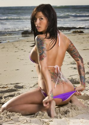 sexy tattooed babe on beach wearing bikini